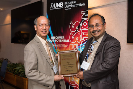 In 2015 UNB Fredericton's faculty of business administration received an excellence in research award at the Atlantic Business Schools conference. Here, conference chair, Dr. Basu Sharma, is presenting the award to Dr. Devashis Mitra, dean of the faculty of business administration.