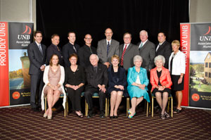 2011 Proudly UNB Awards Recipients: seated, from left, Cayman Grant, Chris Coldwell (representing the Calgary Chapter), John McLaughlin, Carey A. Ryan, Flora Beckett, and Lois Walker Gillin. Standing, from left, Marcel LeBrun, Wayne Long, Justin Rowe, Wyatt Inman, Barry Beckett, Rick Fisher, Gerald O'Brien, Jason Stephen, and Heather Neilson, president of the UNB Associated Alumni.  Photo Credit: Joy Cummings