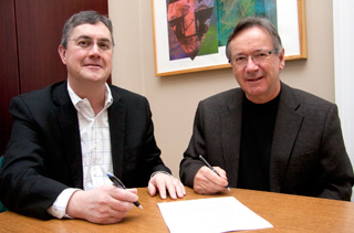 UNB President Eddy Campbell (left) and Barry G. Bisson, President of Shad Valley International sign the MOU. UNB photo.