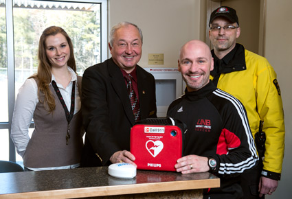 (left to right) Gillian McLean, special assistant to VP Fredericton; Bruce Rogerson, director of security and traffic; and Desmond Dupuis (back), security patrol, present the defibrillator to Miles Pinsent (front), men's soccer coach.
