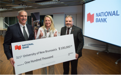 Michael McManus, National Bank's regional manager for Western New Brunswick and Prince Edward Island, presents UNB's Pond Deshpande Centre with a cheque for $100,000.