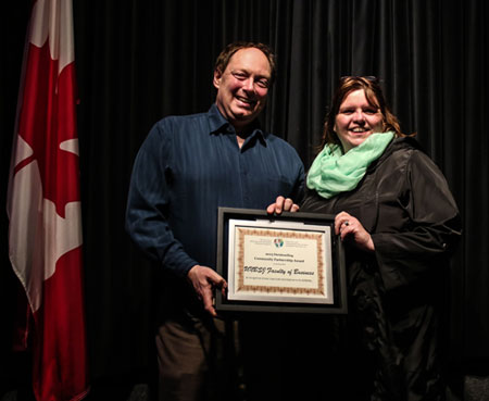 Drs. Rob Moir, Associate Dean (Research and Special Projects) and Shelley Rinehart, MBA Director, receive the Outstanding Community Partnership Award plaque.