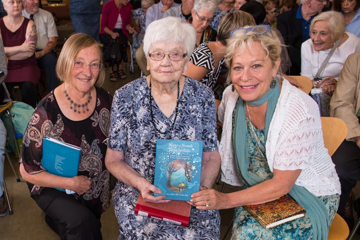 Anne Hunt, Eileen Wallace and Sheree Fitch pose with a copy of Whispers of Mermaids and Wonderful Things at UNB's Harriet Irving Library on Sept. 21, 2017. (Cameron Fitch / Photo UNB)